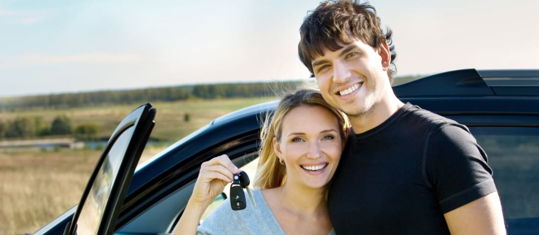 couple smiling while holding a key
